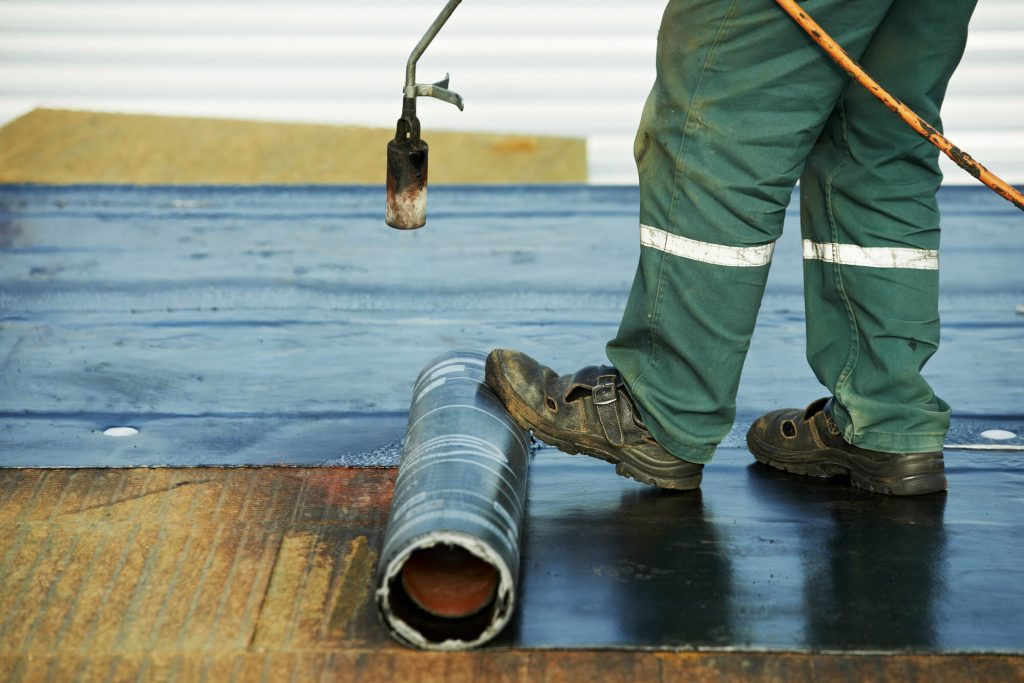 contractor rolls out rubber roofing material onto flat roof