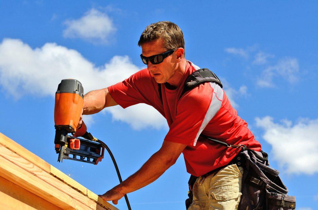 man fastening roof shingles using a nail gun