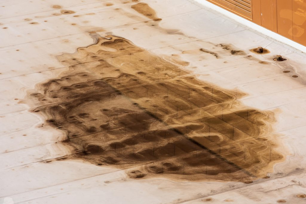 dark brown stains on flat roof caused by ponding water